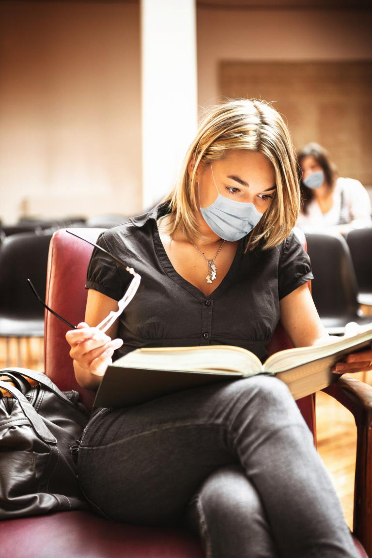 Student wearing protective COVID-19 mask as she studies.